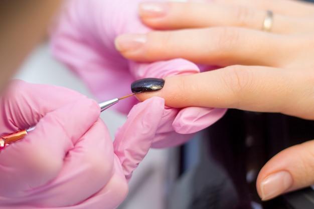 Concetto di cura delle unghie e manicure. le mani del manicure di primo piano nei guanti rosa sta dipingendo lo smalto nero sulle unghie del cliente. Foto Premium