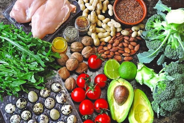 Concetto di dieta chetogenica. un insieme di prodotti della dieta cheto a basso contenuto di carboidrati. verdure verdi, noci, filetto di pollo, semi di lino, uova di quaglia, pomodorini. concetto di cibo sano. keto diet food. Foto Premium