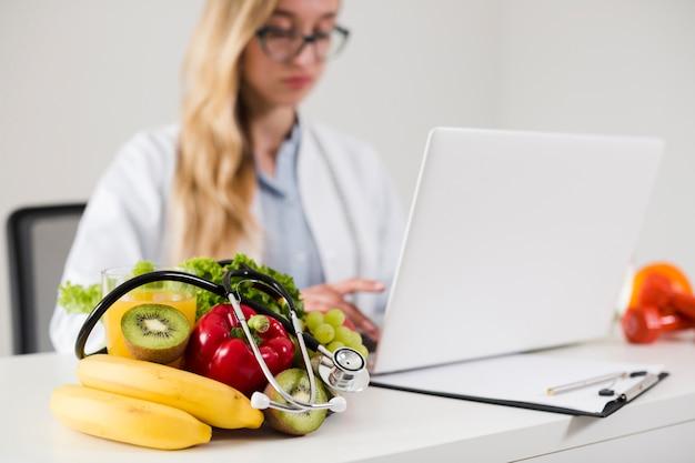 Concetto di dieta con scienziato femminile e cibo sano Foto Gratuite