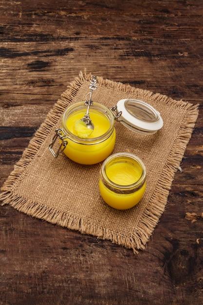 Concetto di dieta di grassi sani o piano di stile paleo. vaso di vetro, cucchiaio d'argento su tela di sacco vintage. Foto Premium