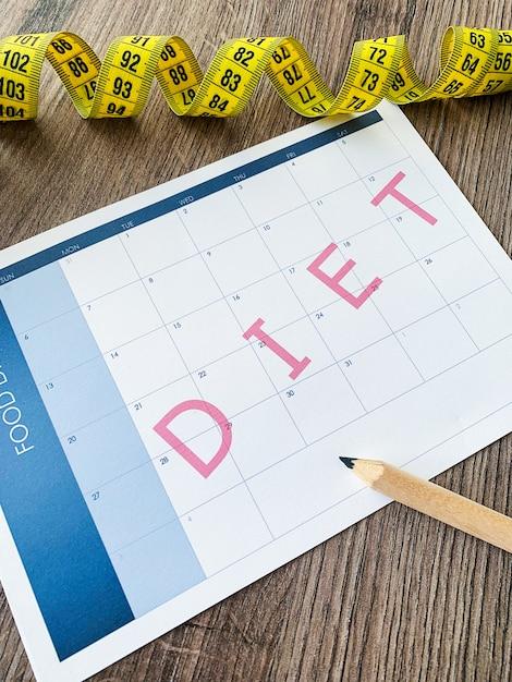 Concetto di dieta. nastro di misurazione e piano dietetico Foto Premium
