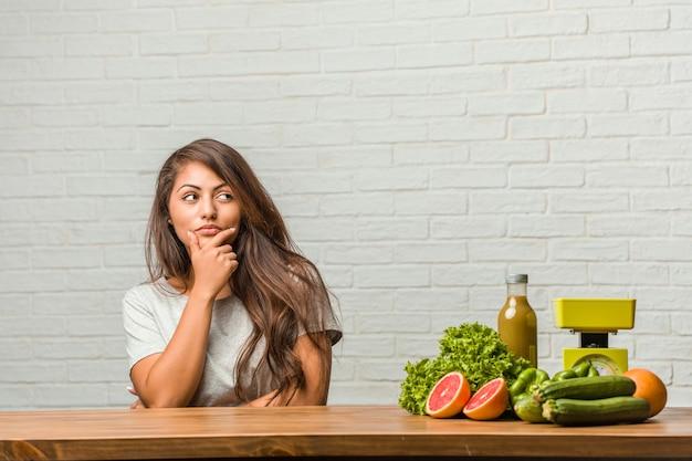 Concetto di dieta ritratto di una giovane donna latina in buona salute che pensa e che osserva in su Foto Premium