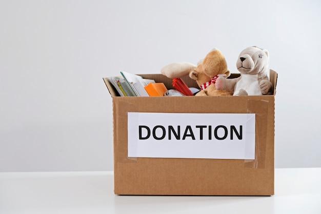 Concetto di donazione. scatola in pieno di libri e di giocattoli sulla tavola bianca. fai una donazione per i bambini, per favore Foto Premium