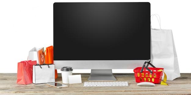 Concetto di e-commerce. schermo del monitor del computer sul tavolo con accessori per lo shopping Foto Premium