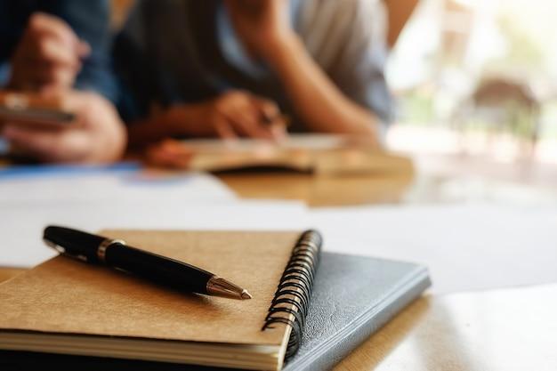 Concetto di educazione. studio studente e brainstorming campus concept. primo piano di studenti che discutono il loro tema su libri o libri di testo. messa a fuoco selettiva. Foto Gratuite