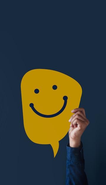 Concetto di esperienze del cliente. la gente moderna ha alzato la mano per dare un'icona faccia felice e una recensione positiva sulla carta. sondaggi sulla soddisfazione del cliente. vista frontale Foto Premium
