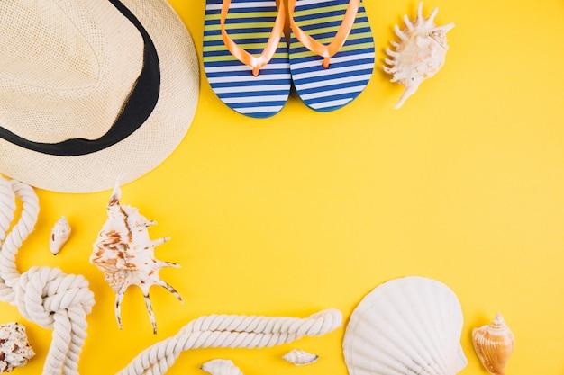 Concetto di estate accessori da viaggio: un cappello di paglia, una macchina fotografica, una corda, conchiglie e pantofole. Foto Premium