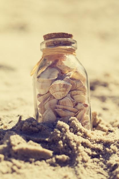 Concetto di estate o di vacanza. seashells in bottiglie sulla sabbia. tonificante. Foto Gratuite