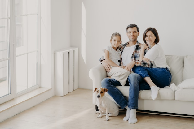 Concetto di famiglia, solidarietà e relazione. l'uomo felice abbraccia la figlia e la moglie, si siede sul comodo divano bianco nella stanza vuota, il loro animale domestico si siede sul pavimento, fa un ritratto di famiglia per un lungo ricordo Foto Premium