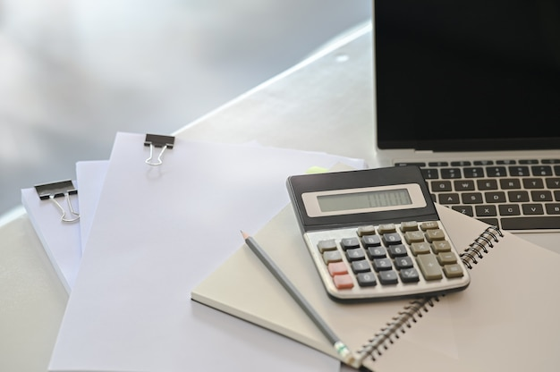 Concetto di finanza, calcolatrice, laptop e lavoro di ufficio sul tavolo ufficio. Foto Premium