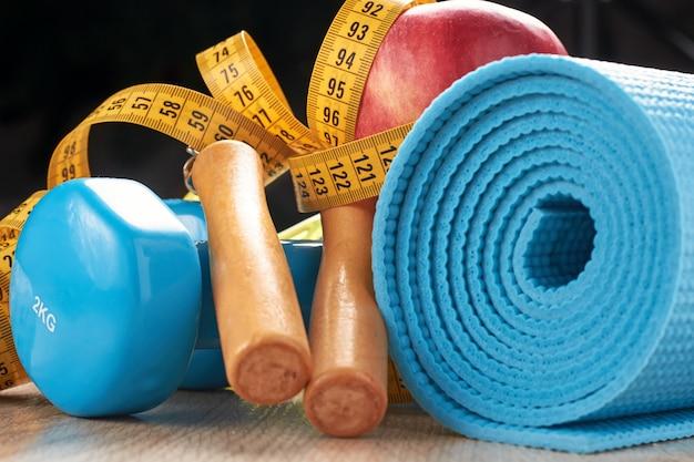 Concetto di forma fisica con manubri blu, tappetino fitness e corda per saltare su uno sfondo scuro Foto Premium