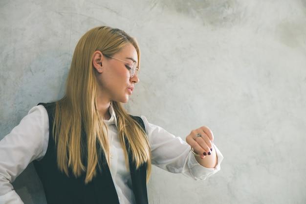 Concetto di gestione del tempo e del business. giovane imprenditrice guardando orologio da polso. il tempo è denaro Foto Gratuite