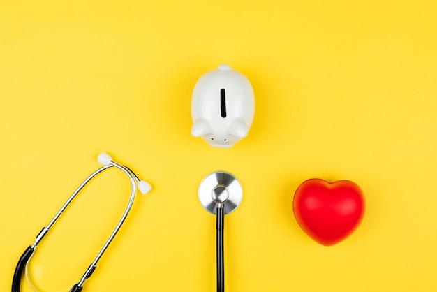 Concetto di giornata mondiale della salute assicurazione sanitaria con cuore rosso, cassa di risparmio e stetoscopio Foto Premium