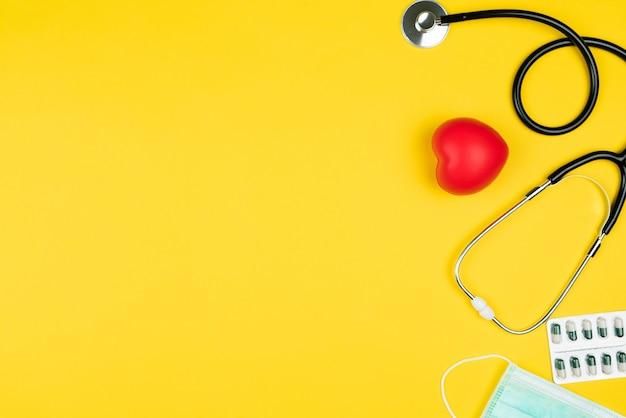 Concetto di giornata mondiale della salute assicurazione sanitaria con cuore rosso, stetoscopio, maschera e medicina Foto Premium