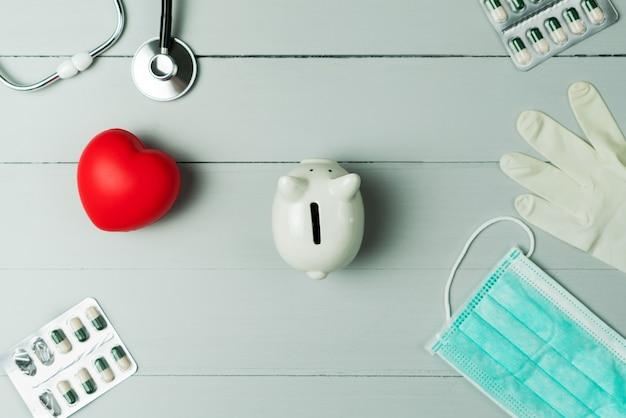 Concetto di giornata mondiale della salute e assicurazione medica sanitaria con cuore rosso e strumento medico su fondo di legno Foto Premium