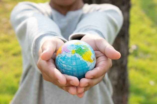 Concetto di giornata mondiale della terra. passi la plastica della tenuta del pianeta terra sul fondo della natura salvo il concetto del mondo. Foto Premium