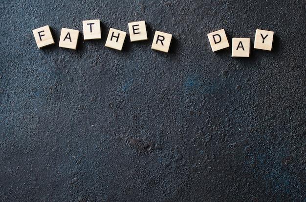 Concetto di giorno del padre. lettere di legno su sfondo scuro. Foto Premium