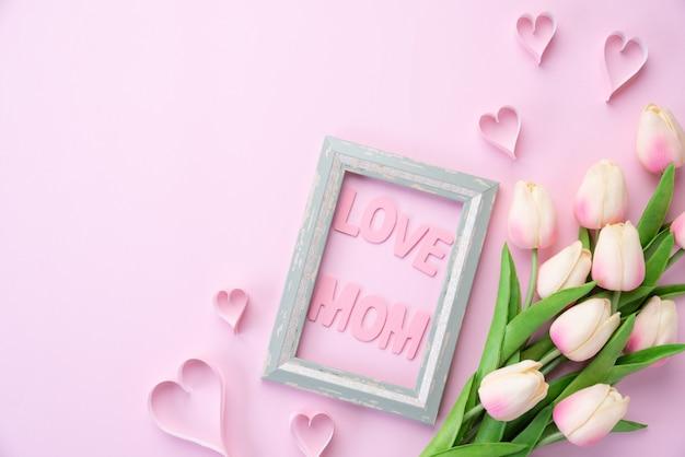 Concetto di giorno di madri felice. fiore tulipano rosa con cuore di carta e cornice Foto Premium