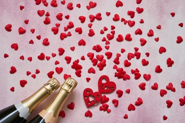 Concetto di giorno di san valentino. bottiglie di champagne con cuori rossi su sfondo rosa. Foto Premium