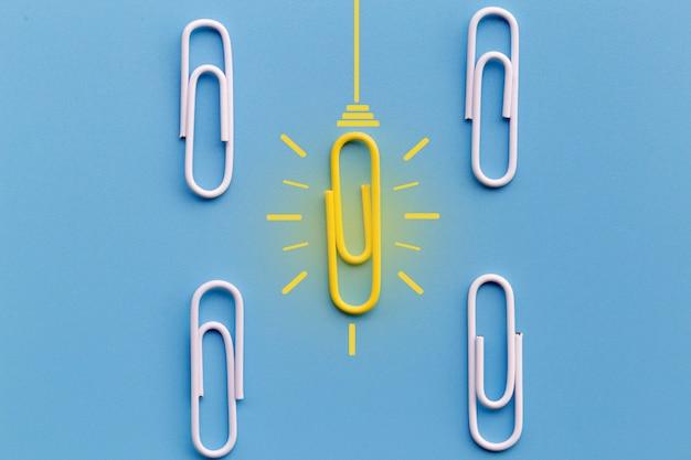 Concetto di grandi idee con graffetta, pensiero, creatività, lampadina su fondo blu, nuovo concetto di idee. Foto Premium