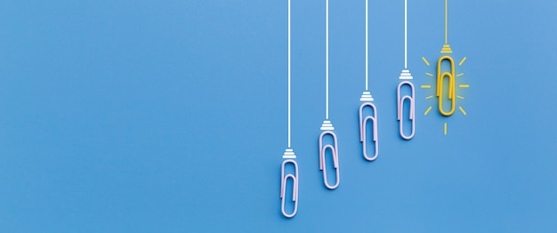 Concetto di grandi idee con la lampadina di creatività di pensiero della graffetta su fondo blu Foto Premium