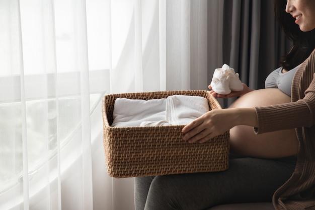 Concetto di gravidanza, maternità e aspettativa - donna incinta che prepara le scarpe vestite e piccole per il bambino non ancora nato. Foto Premium