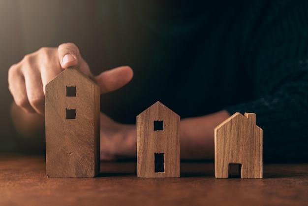 Concetto di idee di decisione di progettazione della casa con il modello di legno di forma della casa della scelta della mano dell'uomo sulla tavola marrone Foto Premium