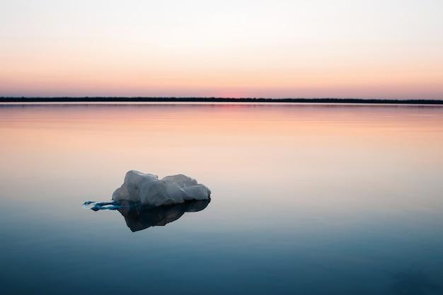 Concetto di inquinamento, creativo. sacchetto di plastica che galleggia nell'oceano Foto Premium