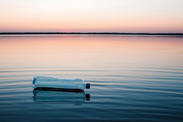 Concetto di inquinamento, creativo. una bottiglia di plastica che galleggia nell'oceano Foto Premium