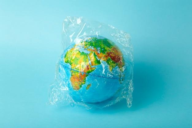 Concetto di inquinamento del sacchetto di plastica. globo terrestre in un sacchetto di plastica su uno sfondo colorato. oceani di inquinamento di plastica e rifiuti, natura Foto Premium