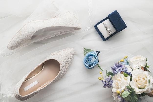 Concetto di matrimonio, scarpe da sposa, anello e fiori Foto Premium