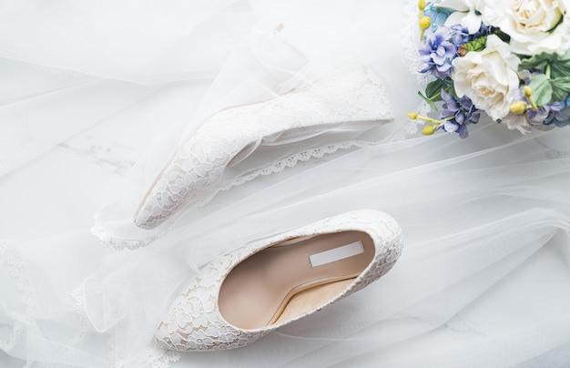 Concetto di matrimonio, scarpe da sposa e fiori Foto Premium