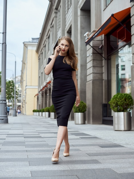 Concetto di moda di strada: corpo pieno ritratto di giovane bella donna che cammina in città. Foto Premium