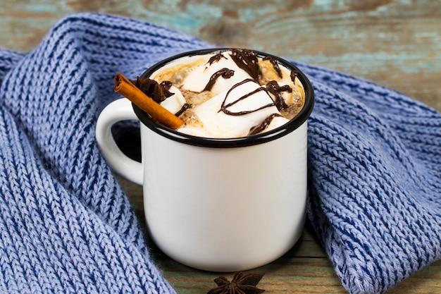 Concetto di natale, cioccolata calda o cacao con marshmallow e spezie, regali di natale, bastoncini di zucchero, ramo di un albero di natale e pigne, sul vecchio tavolo di legno rustico Foto Premium