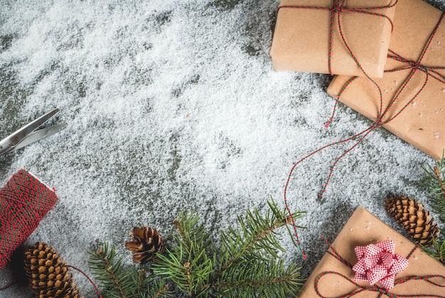 Concetto di natale, priorità bassa della tabella con neve, rami dell'albero di natale, regali o regali, pigne e decorazione Foto Premium