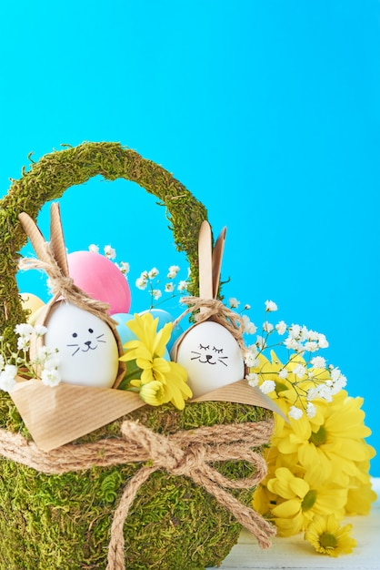 Concetto di pasqua. merce nel carrello delle uova decorata con i fiori su un fondo blu Foto Premium