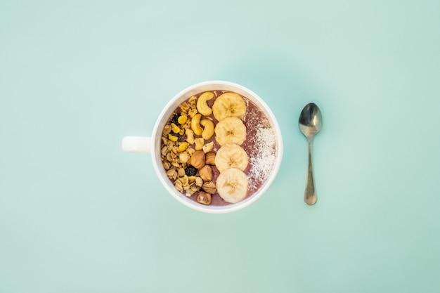 Concetto di pasto sano: una ciotola di frullato di frutta con noci e fette di banana. ciotola acai con cereali, anacardi e nocciole Foto Premium