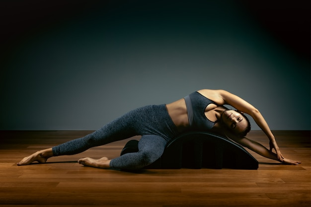 Concetto di pilates, fitness, sport, allenamento e persone - donna che fa le esercitazioni su una piccola botte. concetto di fitness Foto Premium