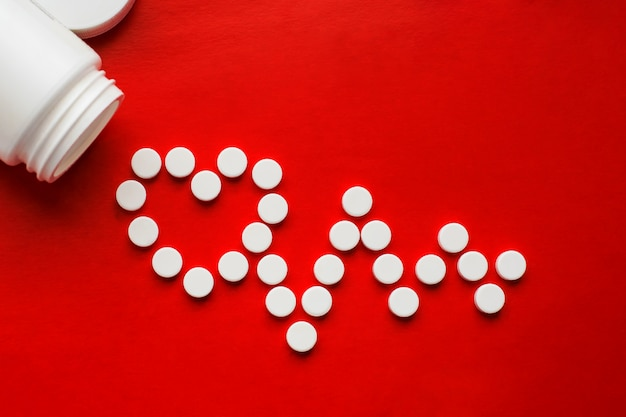 Concetto di pillole per malattie cardiache e cardiovascolari. le pillole bianche dormono abbastanza da un barattolo bianco e formano un cardiogramma e un simbolo del cuore su uno sfondo rosso. copia spazio. sfondo isolato Foto Premium