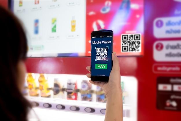 Concetto di portafoglio mobile mani della donna che scansionano il codice qr tramite telefono cellulare con il distributore automatico astuto Foto Premium