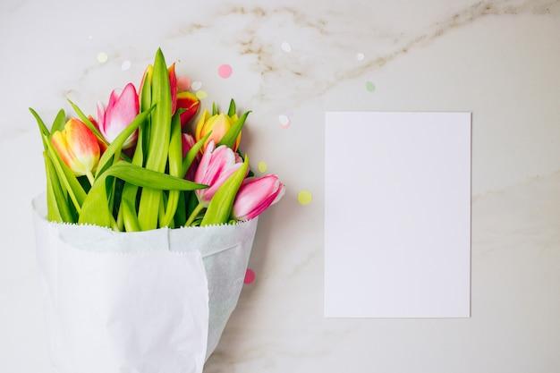 Concetto di primavera tulipani rosa e rossi con bianco pulito bianco per il vostro testo su sfondo di marmo. copia spazio, distesi. Foto Premium