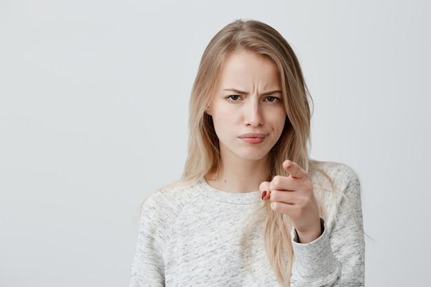 Concetto di pubblicità. donna bionda europea allegra emozionante che indossa le sopracciglia aggrottanti le sopracciglia della maglietta a maniche lunghe e che indica dito indice Foto Gratuite