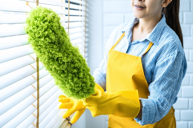 Concetto di pulizie e pulizia, giovane donna felice in guanti di gomma gialli che pulisce polvere usando la scopa di piume mentre si pulisce sulla finestra a casa Foto Premium