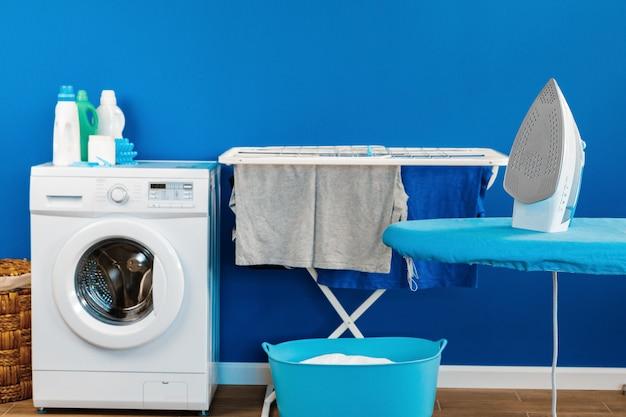 Concetto di pulizie. lavatrice e asse da stiro Foto Premium
