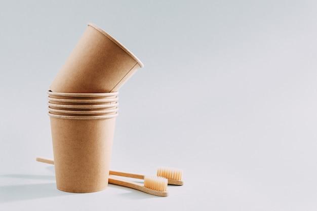 Concetto di rifiuti zero con bicchieri di carta e spazzolini da denti Foto Premium