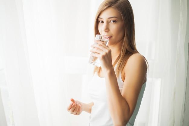 Concetto di salute. pillola e bicchiere d'acqua della tenuta della giovane donna Foto Premium
