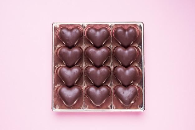 Concetto di san valentino. caramelle al cioccolato, cuori su uno sfondo rosa Foto Premium
