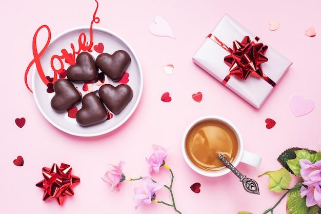 Concetto di san valentino. caramelle e caffè al cioccolato, cuori su uno sfondo rosa. spazio piatto per la copia. biglietto d'auguri e regalo. Foto Premium