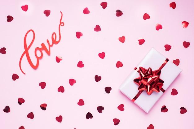 Concetto di san valentino. sfondo rosa con cuori rossi e regalo. spazio piatto per la copia. biglietto d'auguri e regalo. Foto Premium