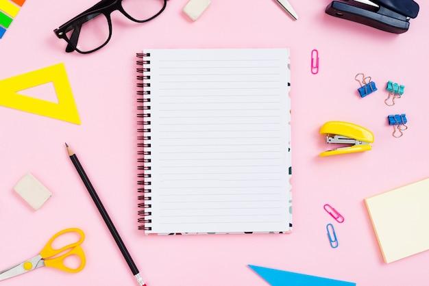 Concetto di scrivania vista dall'alto con sfondo rosa Foto Gratuite